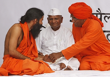 Ramdev speaks with social activist Swami Agnivesh as Anna Hazare listens.