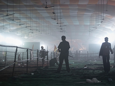 A policeman stands under an empty smoke-filled marquee after supporters of Ramdev were dispersed by tear gas from the Ramlila grounds