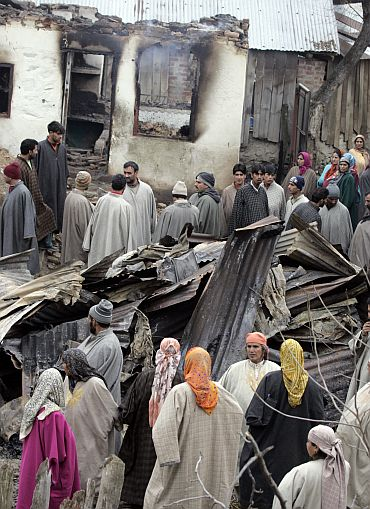Kashmiri villagers stand near damaged houses after a gun battle in Botango,near Srinagar in January, 2009. Two militants were killed in an encounter with security forces and four residential houses were destroyed