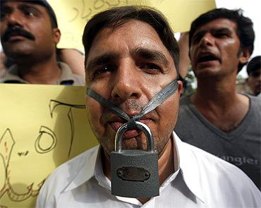 A journalist hangs a lock across his lips during a protest against Saleem Shahzad's death
