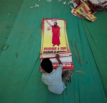 A worker sorts through posters of yoga guru Swami Ramdev