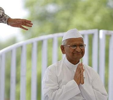 Veteran social activist Anna Hazare clasps his hands together as he greets supporters after arriving for his hunger strike at Rajghat in New Delhi