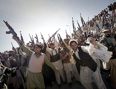 Members of the local Lashkar (tribal militia-men), hold their weapons while dancing in a show-of-force in Khar, located in Pakistan's Federally Administered Tribal Areas