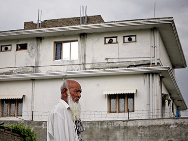 A resident walks past the compound Al Qaeda chief Osama bin Laden was killed by US forces in Abbottabad, near Islamabad
