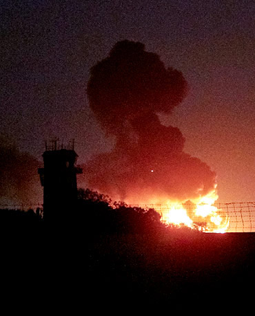 A plume of smoke rises after an explosion triggered by terrorists at the Mehran naval aviation base in Karachi