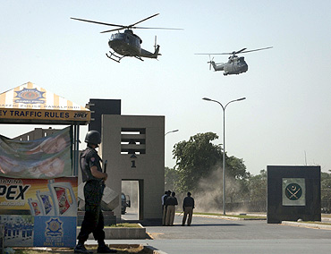 Military helicopters fly over the entrance to Pakistan's army headquarters after an attack by armed terrorists in Rawalpindi in 2009