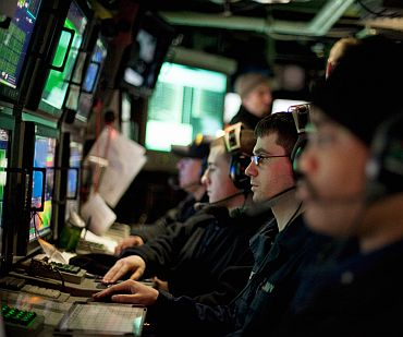 Navy sailors watch their sonar screens as they work in the control room of USS New Hampshire