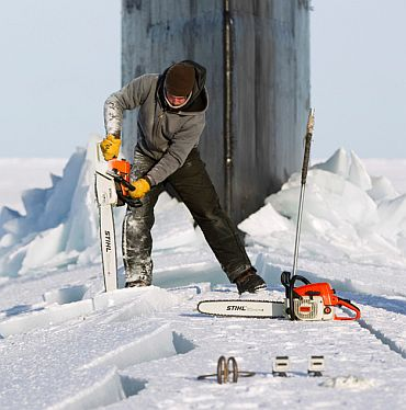 Employee Keith Magness uses a chainsaw to cut through ice to access the hatches of USS Connecticut