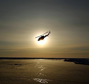A helicopter flies over Arctic ice towards the Applied Physics Laboratory Ice Station