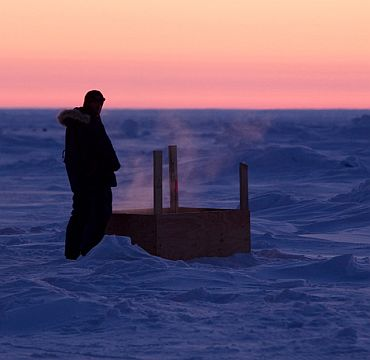 A man urinates into a box as the sun sets over Arctic ice