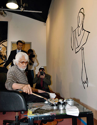 M F Husain paints during an exhibition in New York