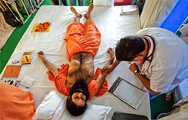 A doctor checks the pulse of Swami Ramdev