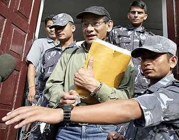 Sobhraj comes out of a court in Kathmandu surrounded by security personnel