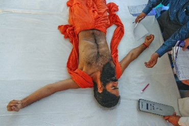 Ramdev, lying on stage, gets a medical check-up during his fast against corruption
