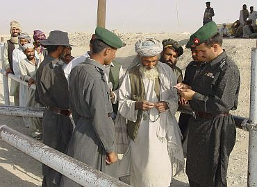 Pakistani para-military soldiers check travel documents of Afghans entering Pakistan at the border of Chaman, near Quetta