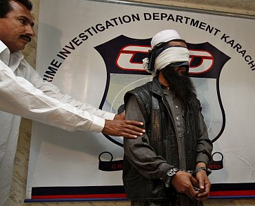 A policeman in plain clothes showcases a blindfolded and handcuffed Mullah Abdul Ghani Baradar in Karachi