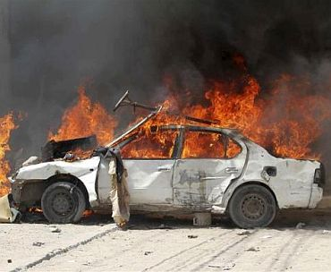 A car burns outside Hotel Madina during a protest in support of Prime Minister Mohamed Abdullahi Mohamed, in the streets of Somalia's capital Mogadishu