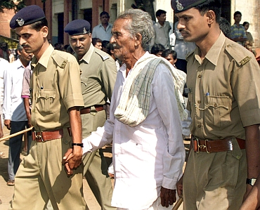 Policemen escort one of the prime suspects in the Gujarat riots case to a court in Nadiad in November 2003