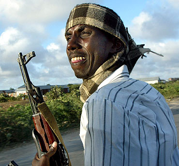A Somali gunmen sits at the back of a pickup truck as their drive through the streets of Mogadishu