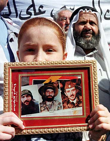 A boy holds pictures of Chechen leaders (L-R Salman Raduyev, Shamil Basayev and Dzhakhar Dudayev) during a protest in Amman