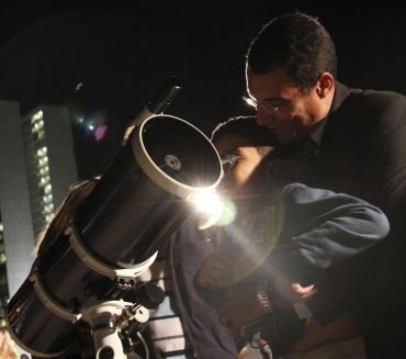 A man helps a boy look through a telescope during a total lunar eclipse
