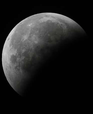 The moon is partially visible during a total lunar eclipse over Ahmedabad