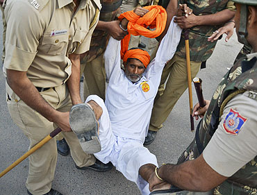 A supporter of yoga guru Baba Ramdev is detained by police at the Ramlila grounds