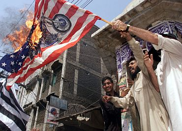Anti-US demonstrators wave a burning American flag during a protest rally in Peshawar