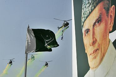 Pakistani army helicopters fly past the portrait of country's founder Mohammad Ali Jinnah during the National Day military parade in Islamabad