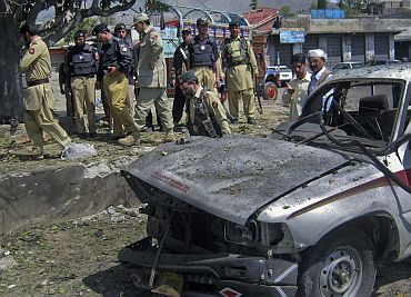 Policemen and paramilitary forces stand at the scene of a suicide bomb blast in Dir, northwest Pakistan