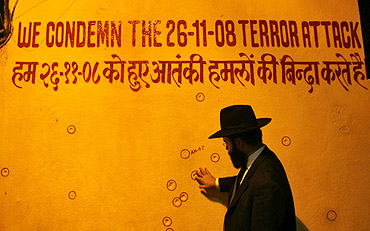 A rabbi touches a wall riddled with bullet holes in front of Nariman House