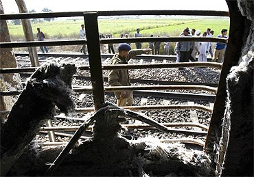 Onlookers stand near the burnt carriage of the Samjhauta Express train after the blast