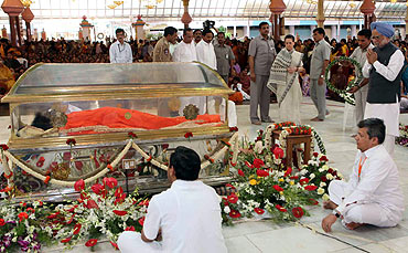 Prime Minister Manmohan Singh and Congress chief Sonia Gandhi pay their last respects to Sai Baba