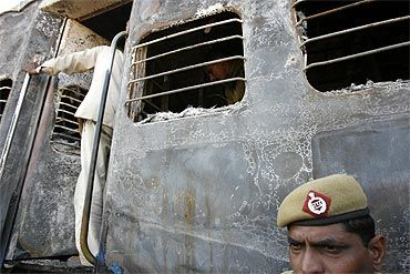 A policeman stands outside a burnt carriage of a Samjhauta Express train