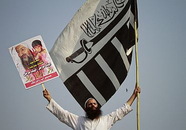 A JuD supporter holds a party flag and an image of Al Qaeda leader Osama bin Laden during anti-American rally in Lahore