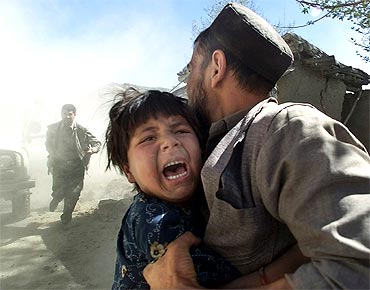 An Afghan girl screams as she is held her father as a sharp aftershock hits the country