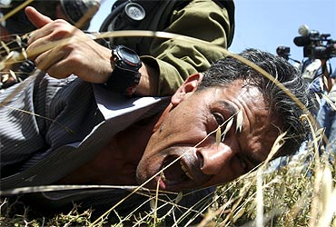 A protester shouts as Israeli border police officers detain him during clashes