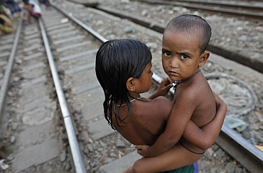 Nafisa plays with her sister in a slum beside a railway line in Dhaka