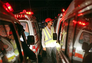 A rescue worker stands between ambulances lined outside the Mehran naval aviation base