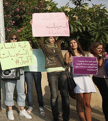Activists hold placards, expressing solidarity with Saudi women in their fight for basic civil rights and their right to drive, during a protest in front of the Saudi embassy in Beirut