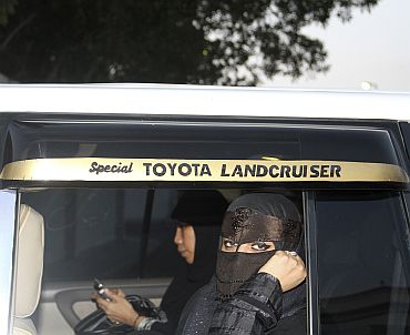 A Saudi woman looks out from the back seat of a car in Jeddah