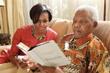 First Lady Michelle Obama and former SA president Nelson Mandela read his latest book Nelson Madela by Himself at his house in Johannesburg