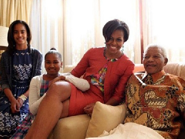 Michelle Obama, accompanied by her daughters, Malia and Sasha, meet Mandela at this home