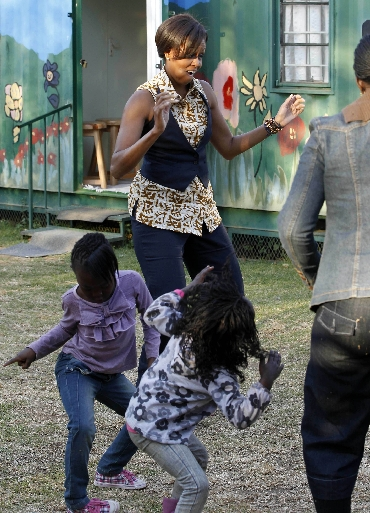 Michelle Obama dances with children as she visits the Emthonjeni Community Center in Zandspruit Township, Johannesburg