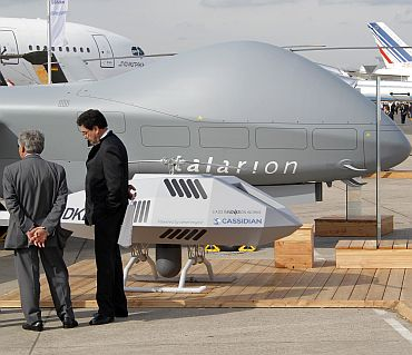 Visitors look at Eurocopter drones Talarion and Cassidan during the 49th Paris Air Show