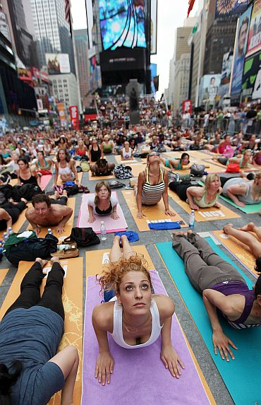 Naty Horev (C) and other enthusiasts perform yoga in Times Square