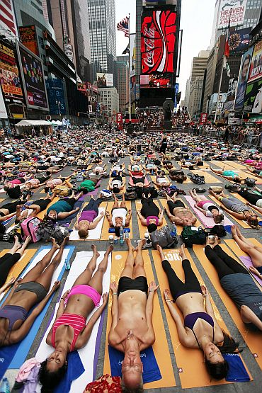 Enthusiasts perform yoga in Times Square during an event marking the summer solstice
