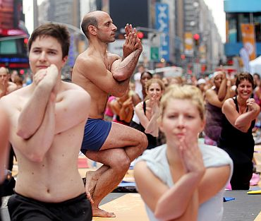 Enthusiasts perform yoga in Times Square