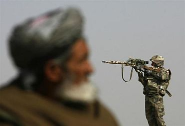 A sniper looks through his rifle's scope while keeping watch over Qarabagh district, north of Kabul