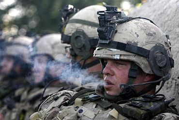 A soldier smokes during a lull in fighting against Taliban insurgents in Sangasar, Zari district